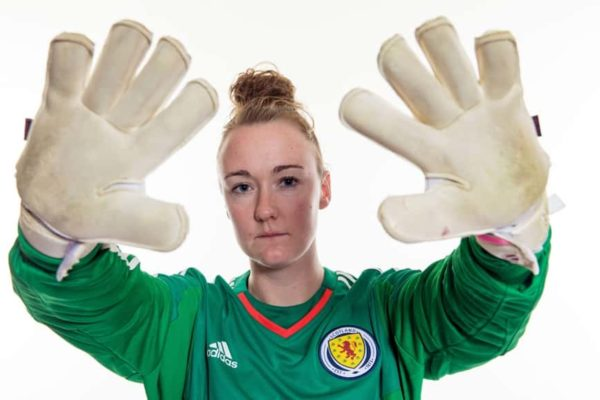 Goal keeper showering her goal keeper gloves
