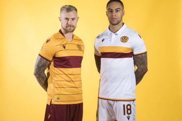 Two football players pose in kit