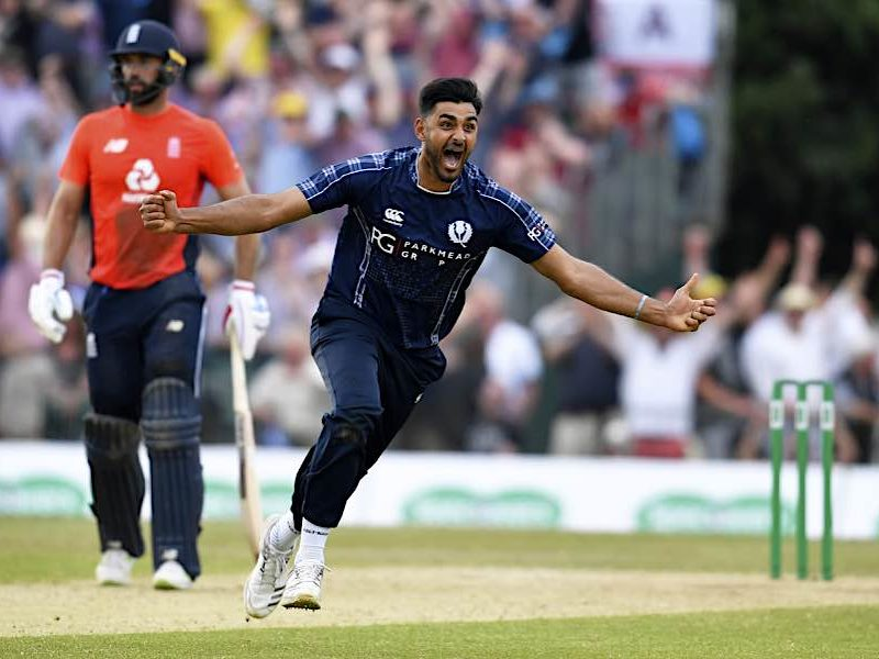 Safyaan Sharif runs with his arms out celebrating Scotland's victory over England by 6 runs